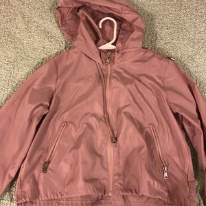 Blush pink windbreaker with pockets and a hood.